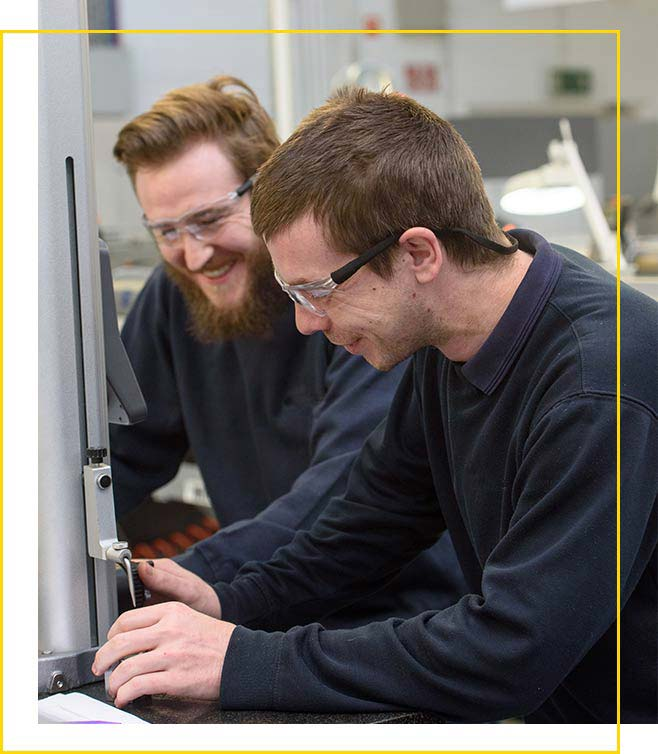 Two Schivo employees working on micromachining a product
